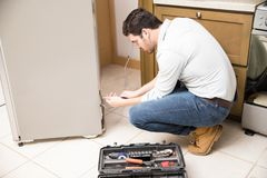 Male electrician repairing a refrigerator. Profile view of an attractive male electrician fixing a refrigerator in a residential kitchen Stock Photography