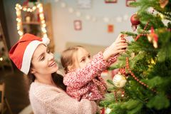 Family of Two Decorating Christmas Tree. Profile view of attractive women wearing knitted sweater and Santa hat holding her cute little daughter on arms while Royalty Free Stock Photography