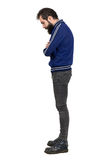 Profile view of bearded hipster in blue tracksuit jacket looking down with crossed arms Royalty Free Stock Photography