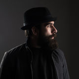 Profile view of bearded man wearing hat looking away. Low key dark shadow portrait over black background stock photo