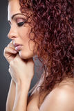 Profile view of a beauty with curly red hair Royalty Free Stock Image