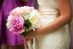 Profile view of bride holding wedding bouquet of flowers Stock Images