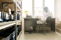 Inventory at Factory Warehouse. Profile view of concentrated bearded technician wearing white coat sitting at desk and taking necessary notes after completion of Royalty Free Stock Photos
