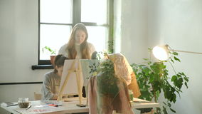 Profile view of a couple of adults working on a painting at an art school 4k 20s stock footage