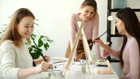 Profile view of a couple of adults working on a painting at an art school 4k 20s. Profile view of a couple of adults working on a painting at an art school. 4k stock footage