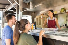 Customers making line in a food truck. Profile view of a couple of customers lining up in front of a food truck and buying some food royalty free stock photos