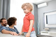 Portrait of Adorable Little Boy. Profile view of cute curly boy wearing red T-shirt standing on couch and looking away with concentration, his middle-aged Stock Photography
