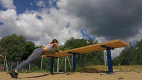 Profile view of a female athlete doing some tricep dips on a park bench.  stock video footage