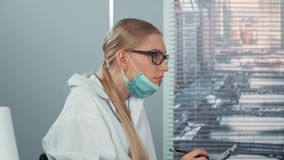 Profile view of female scientist in eyeglasses and lab coat writing notes and then drawing attention on something else. In front. She putting on protective mask stock video