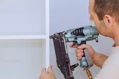 Profile view of a good looking young handyman making some air gun holes in a wall and installing a shelf. Profile view of a good looking young handyman making royalty free stock image