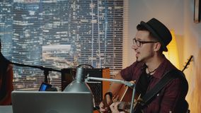Profile view of handsome hipster singing into microphone and playing the guitar in home recording studio stock footage