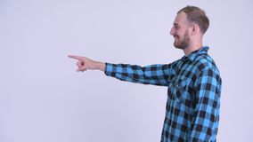 Profile view of happy bearded hipster man pointing finger. Studio shot of bearded hipster man against white background stock video