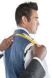 Profile view of man getting measured by tailor Royalty Free Stock Image