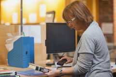 Profile view of mature librarian scanning a book. Behind the desk Stock Photography