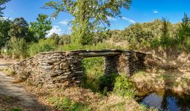 Old antique stone bridge over stream Stock Photo