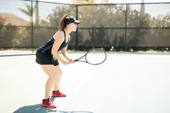 Professional female tennis player training on court. Profile view of professional female tennis player standing on the base line ready to play Royalty Free Stock Photography