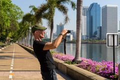 Profile view of senior tourist man wearing cap while taking pict. Ures at peaceful park in Bangkok Thailand stock photography