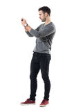 Profile view of serious young casual man holding cellphone taking photo. Full body length portrait isolated over white studio background Royalty Free Stock Photo