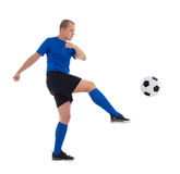 Profile view of soccer player in blue kicking ball isolated on w Stock Photo