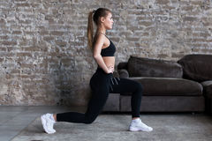 Profile view of sporty girl doing lunges working-out leg muscles and glutes in loft interior royalty free stock image