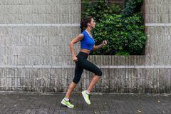 Profile view of a sporty young woman working out outdoors. Fitness girl running on sidewalk. royalty free stock images