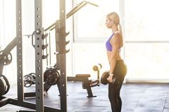 Profile view standing woman in gym, holding dumbbells stock images