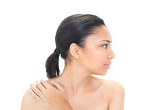 Profile view of a stern black haired model holding her shoulder Royalty Free Stock Photo