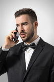 Profile view of upset angry wealthy man on the phone looking away Stock Images