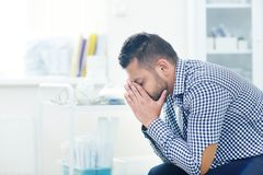 Hopeless Diagnosis of Young Patient. Profile view of upset young patient covering his face with hands after his highly professional physician revealed him Stock Image