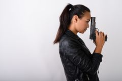 Profile view of young Asian woman holding handgun against white royalty free stock photo
