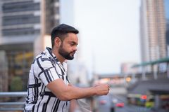 Profile view of young bearded Indian man in the city outdoors. Portrait of young bearded Indian man exploring in the city outdoors stock photography