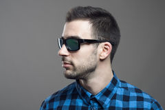 Profile view of young bearded man in plaid shirt wearing sunglasses looking away. Over gray studio background Stock Images