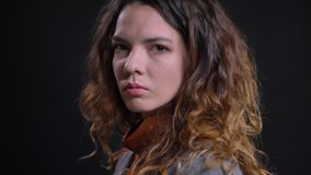 Profile view of young caucasian female with curly brown hair turning and looking at camera with a serious facial. Expression stock footage