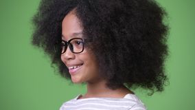 Profile view of young cute African girl with Afro hair smiling stock footage