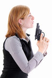 Profile view of young woman holding a pistol gun Royalty Free Stock Image