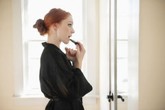 Profile view of a young woman in robe applying lipstick Royalty Free Stock Images