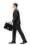 Profile of walking with suitcase business man Stock Photo