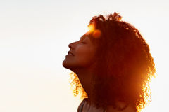 Profile of a woman with afro silhoutted against evening sun Royalty Free Stock Images