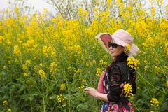 Profile of a woman. A beautiful woman was showing her profile in the oilseed rape flower field Royalty Free Stock Images