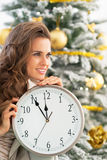 Profile woman with clock near christmas tree Royalty Free Stock Images
