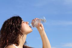 Profile of a woman drinking water from a plastic bottle Stock Photos
