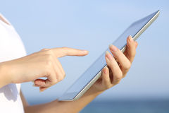Profile of a woman hands holding and browsing a digital tablet on the beach. With the sky in the background royalty free stock photos