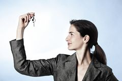 Profile of woman holding key between fingers Stock Photography