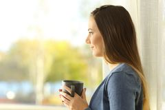 Profile of a woman looking through a window. Side view portrait of a serious pensive woman looking through a window at home Stock Photos