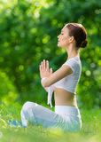 Profile of woman in lotus position prayer gesturing Stock Photos