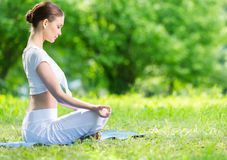 Profile of woman in lotus position zen gesturing. Profile of woman who sits in lotus position zen gesturing. Concept of healthy lifestyle and relaxation Royalty Free Stock Images