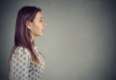 Profile of a woman with open mouth. Profile of a young woman with open mouth talking isolated on gray wall background stock photography