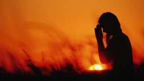 Profile of a woman in prayer at sunset stock images