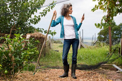 Profile of woman with rake and phone Royalty Free Stock Photo