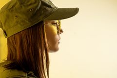 Profile of woman`s in soldier`s suit on yellow background royalty free stock images